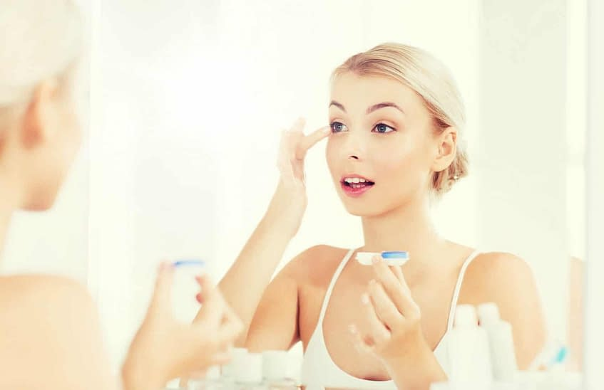 blonde woman putting contact lens in eye