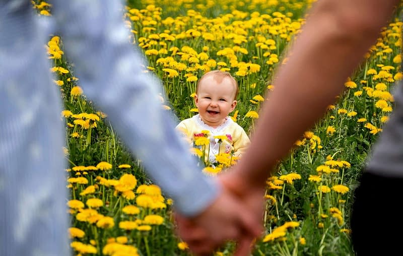 first eye exam happy baby in field with parents
