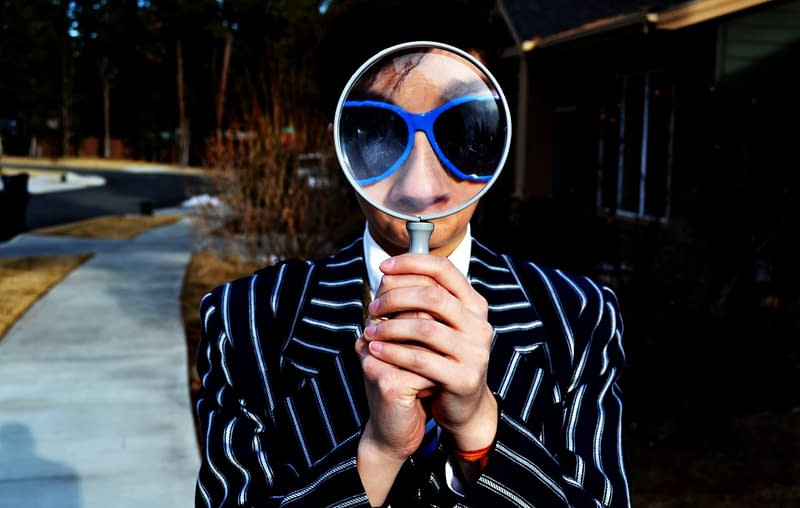 low vision man in striped suit with magnifying glass