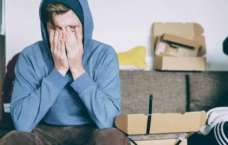 ocular migraine headache young man with headache wearing hoodie
