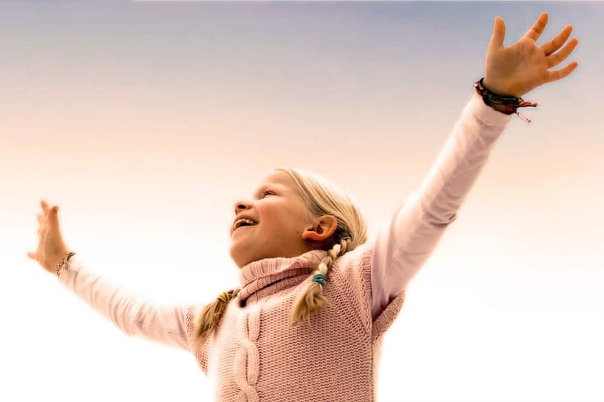 girl raising arms in air